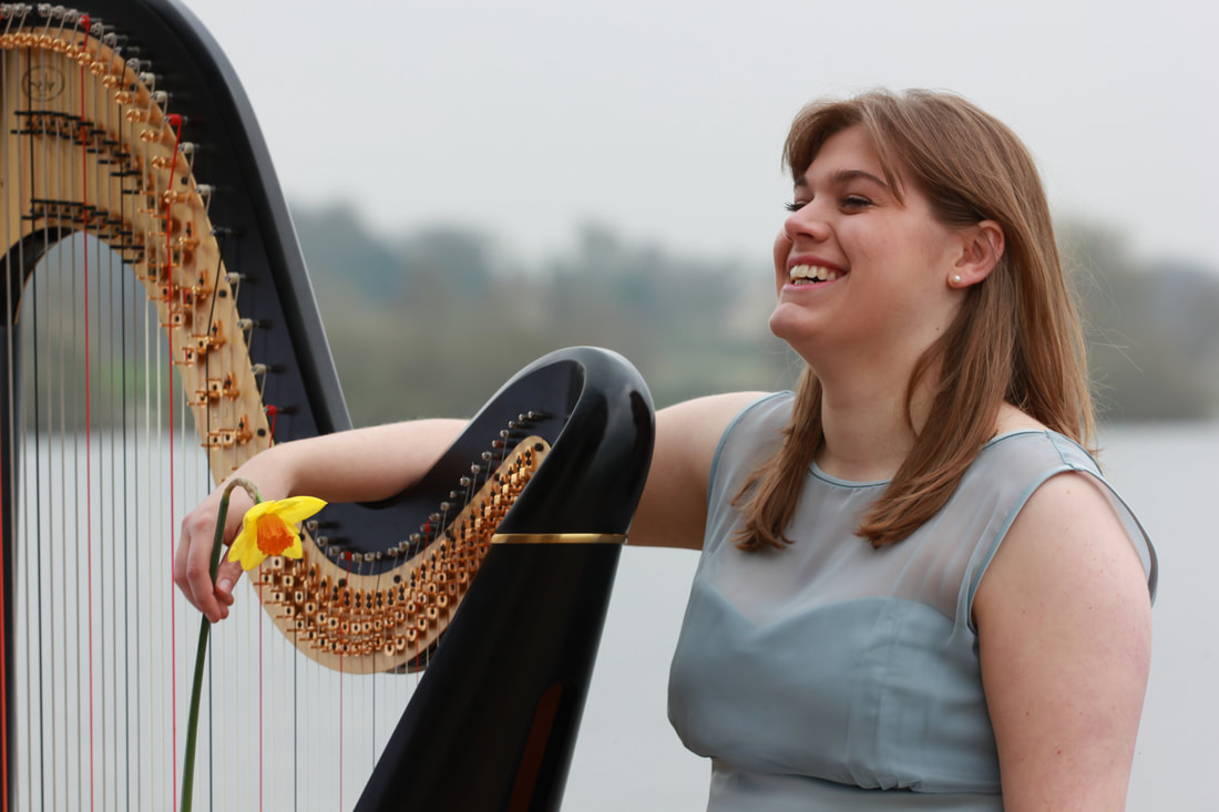 harpist with daffodil at rutland water